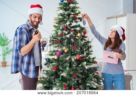 Young family decorating christmas tree on happy occasion