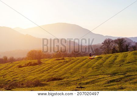Sunset landscape field and mountains, paraglider exercises to fly