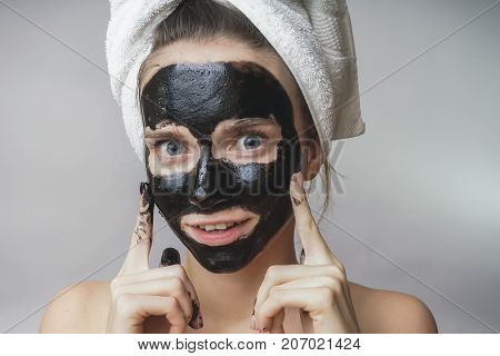 Happy joyful woman applying black mask on face.Skin care,clean pores,exfoliation