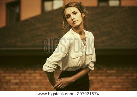 Young fashion business woman walking in city street. Stylish female model in white blouse outdoor