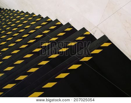 Yellow line on the black step. Warning color at staircase.