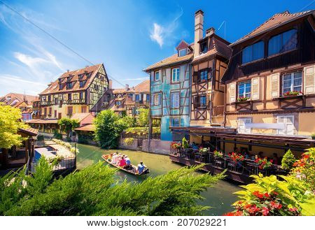 Beautiful view of the historic town of Colmar, also known as Little Venice, with tourists taking a boat ride along traditional colorful houses on idyllic river Lauch in summer, Colmar, Alsace, France on July 22, 2017