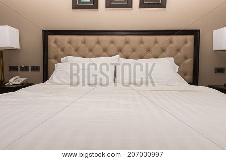 white bedding and pillow in hotel room, pillows on the bed, two pillows in hotel, bed in hotel, bed white color, pillows white color, hotel vintage