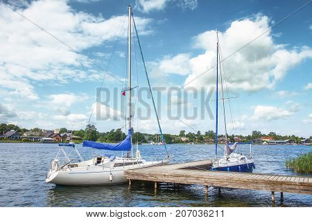 Yachts on lake on clear summer day. White yachts or boats against blue sky with clouds.