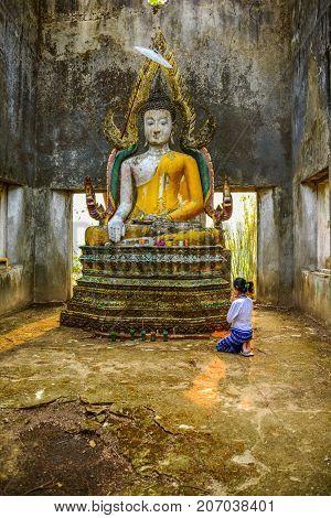 Kanchanaburi Thailand - April 13 2014: Buddhist tourist woman worshiping old Buddha image in ruined buddhist church in Kanchanaburi Thailand