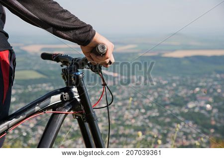 Close-up of a rider's hand on a mountain bike handlebars with shallow depth of field. against the background of the city