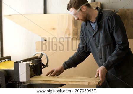 Professional woodworker in protective goggles making wooden parts for custom furniture on machine tool. Workman working at thickness planer machine in carpentry. Producing lumber on own small sawmill