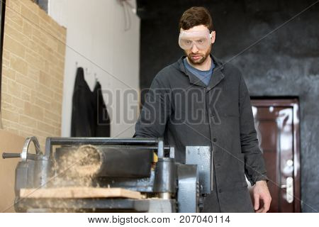 Carpenter in safety glasses standing near machine tool throwing out wooden sawdust while reducing thickness of hardwood board. Small business owner, furniture manufacturer, woodworking industry worker