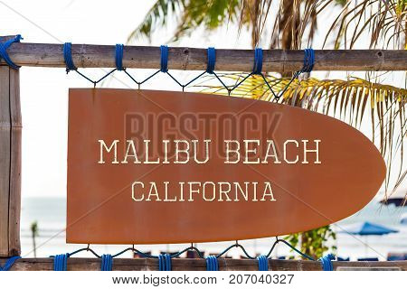 Orange vintage signboard in shape of surfboard with Malibu Beach California text for surf spot and palm tree in background. Vacation and travel concept