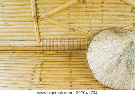 close up a hat made of bamboo and palm leaves on bamboo bench