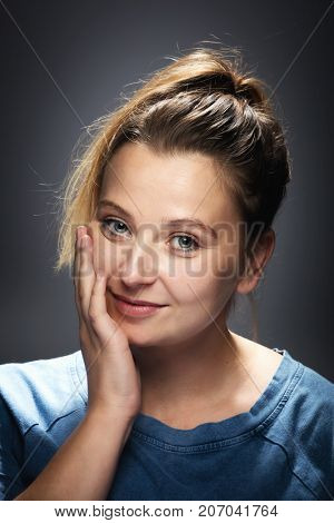 Casual portrait of a smiling, optimistic woman, touching her cheek. Friendly, positive face expression.