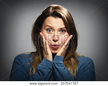 Portrait of a shocked, stressed woman holding her cheecks in a shock.