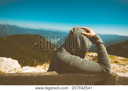 Depressed sad woman at high mountain viewpoint. Female person in hoodie thinking about problems in life. Toned image.
