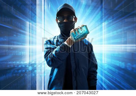Suspicious unknown hacker pose holding mobile phone