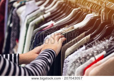 Woman browsing through clothing at second hand street market selective focus on clothes