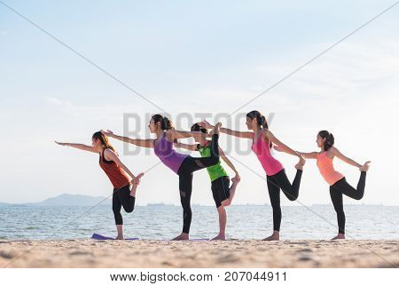 Yoga Class At Sea Beach In Evening ,group Of People Doing Lord Of The Dance Poses With Clam Relax Em