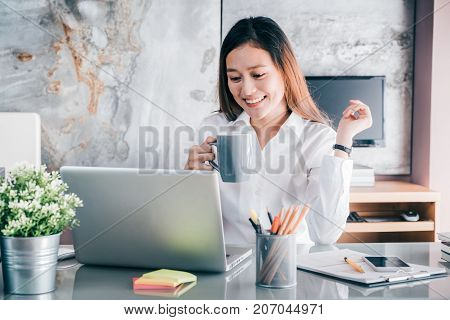 Asian Businesswoman Take A Coffee Break After Working At Laptop Computer On Desk With Smiling Face,h