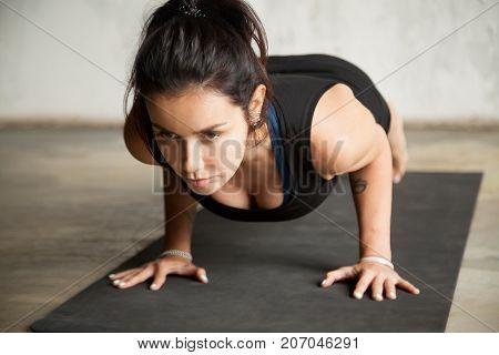 Young attractive woman practicing yoga, doing Push ups, press ups, four limbed staff exercise, chaturanga dandasana pose, working out, wearing black sportswear, indoor close up, studio background