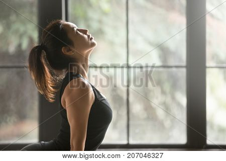 Young attractive sporty woman practicing yoga, stretching in upward facing dog exercise, Urdhva mukha shvanasana pose, working out, wearing sportswear, black top, indoor, window background, side view