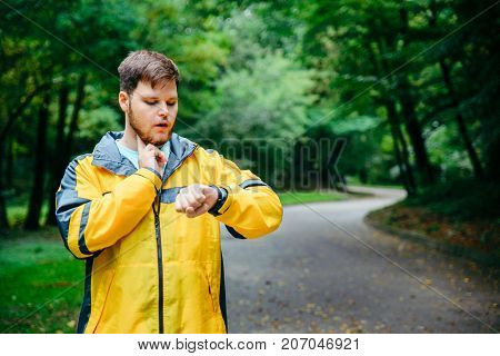 man measuring his pulse while running in autumn park