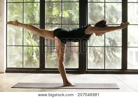 Young attractive woman practicing yoga, standing in Virabhadrasana III exercise, Warrior three pose, working out, wearing sportswear, black shorts and top, indoor full length image, home interior