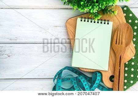 Notepad on chopping board with wooden fork and spoon and the measuring tape on white table recipes food or diet plan for healthy habits shot note background concept