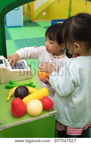 Asian Chinese Little Girls Role-playing At Fruits Store