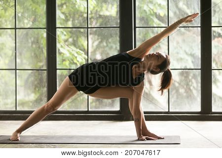 Young woman practicing yoga, stretching in Extended Side Angle exercise, Utthita parsvakonasana pose, working out, wearing sportswear, black shorts, top, indoor full length, home interior background