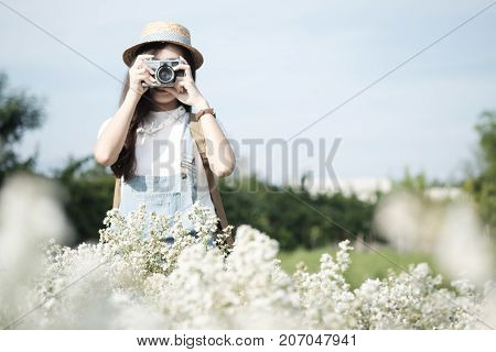 Young woman travel on vacation and using a camera to take photo outdoors at the park. Travel relax and holiday idea concept background.