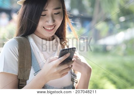 Woman Walk In The Park Outdoor And Using Mobilephone