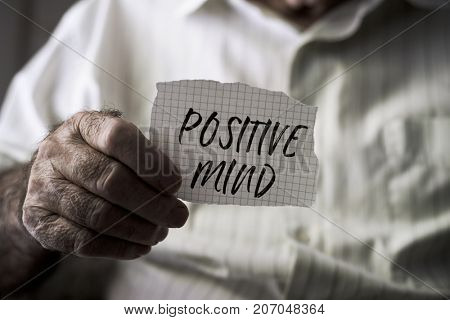 closeup of an old caucasian man with a note in his hands with the text positive mind written in it