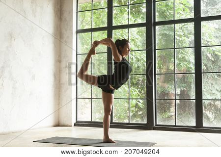Young attractive woman practicing yoga, standing in Natarajasana exercise, Lord of the Dance pose, working out, wearing sportswear, black shorts and top, indoor full length, studio background