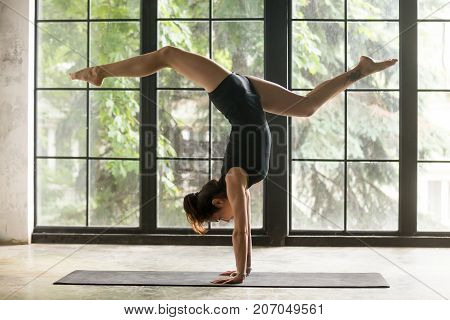 Young woman practicing yoga, standing in Adho Mukha Vrksasana exercise, handstand, Downward facing Tree pose, working out, wearing sportswear, black shorts, top, indoor full length, window background