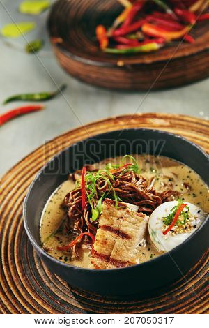 Menu of gastronomic restaurant. Soup with noodles and  coconut milk, pork and egg poached with seeds and fresh herbs in gray bowl on wooden board