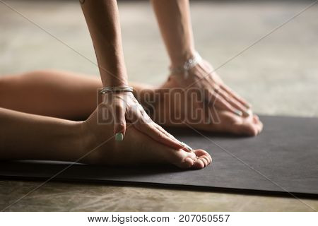 Closeup of female palms resting on heels, woman practicing yoga at home, stretching in Ustrasana exercise, Camel pose, working out wearing wrists bracelets, indoor close up image, floor mat background