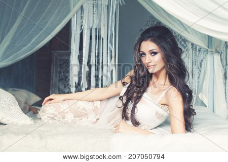 Beautiful Alluring Brunette Woman in White Lingerie Dress on the Bed on Vintage Interior