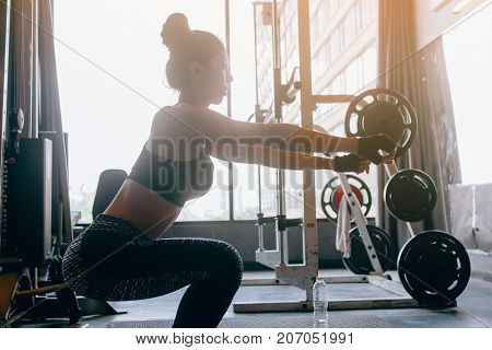 Young Asian Woman In Sportswear Doing Squat At Heath Indoor Gym.