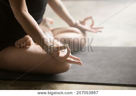 Mudra hand position close up, symbolic or ritual gesture performed by young woman practicing yoga at home, sitting in Padmasana exercise, Lotus pose, working out wearing black clothes, mat background