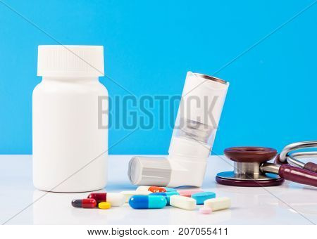 Asthma inhaler with pills and stethoscope medical.