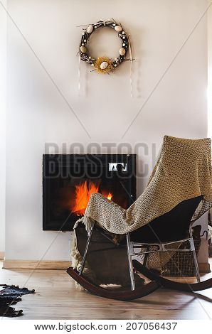 Rocking chair with knit rug, books and cup of tea or coffee before fireplace