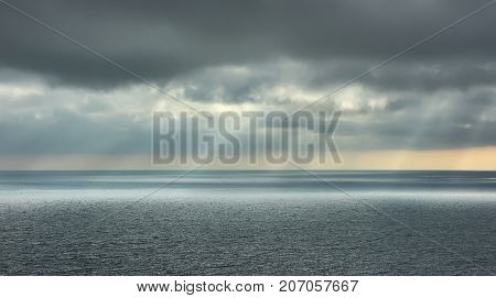 Seascape background. Thunderclouds over the seascape and rays of sun.