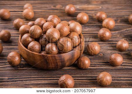 macadamia nuts in bag on wooden backgroun