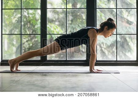 Young attractive woman practicing yoga at home, doing Push ups or press ups exercise, Plank pose, working out, wearing sportswear, black shorts and top, indoor full length, studio background