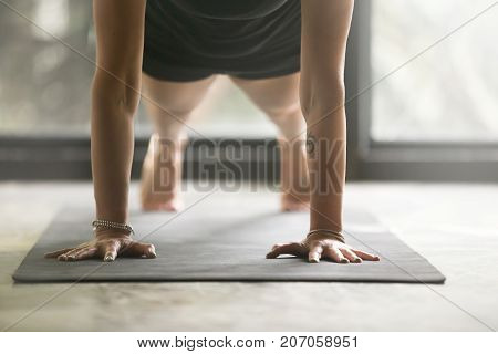 Woman practicing yoga at home concept, doing Push ups or press ups exercise, Plank pose, working out, wearing black sportswear, indoor close up image, studio background