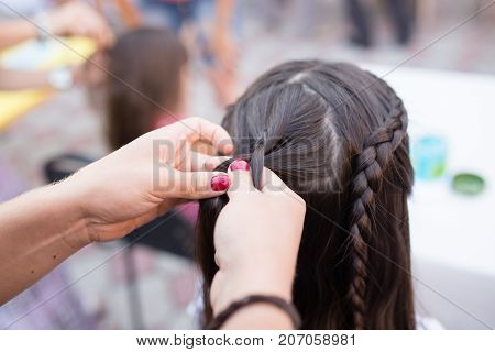 the stylist weaves the female braids on the head .
