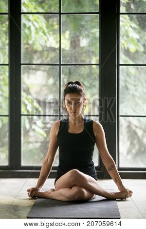 Young attractive woman practicing yoga at home, sitting in Gomukasana exercise, Cow Face pose, working out, wearing sportswear, black shorts and top, indoor full length, studio background
