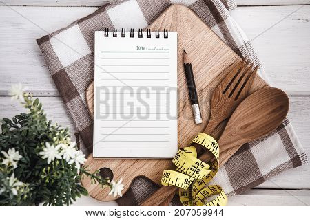 Line Notepad on chopping board with wooden fork and spoon and measuring tape on white table recipes food or diet plan for healthy habits shot note background concept