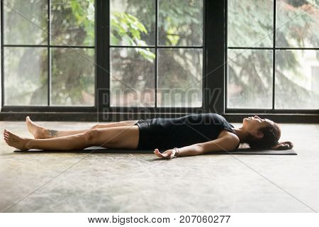 Young attractive woman practicing yoga at home, lying in Savasana exercise, Corpse pose, working out, wearing sportswear, black shorts and top, indoor full length, studio background