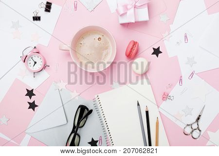 Fashion pink woman workplace background. Coffee macaron office supply gift and clean notebook on pastel desk top view for blogging. Flat lay style. Beautiful morning breakfast.