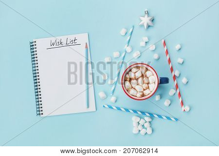 Cup of hot cocoa or chocolate stylish fir tree and wish list on blue background top view. Christmas or new year concept. Flat lay.